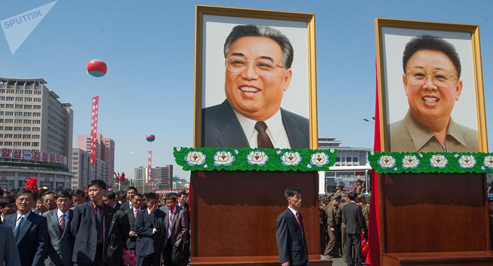 Портреты с изображениями Ким Ир Сена и Ким Чен Ира во время торжественной церемонии открытия нового жилого комплекса на улице Рёмён в Пхеньяне.