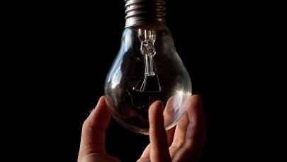 Мужчина держит лампочку. Иллюстративное фото