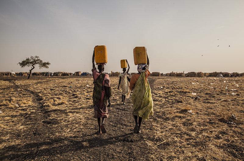 Три женщины несут воду в одном из лагерей для перемещенных лиц в городе Мелут. Южный Судан