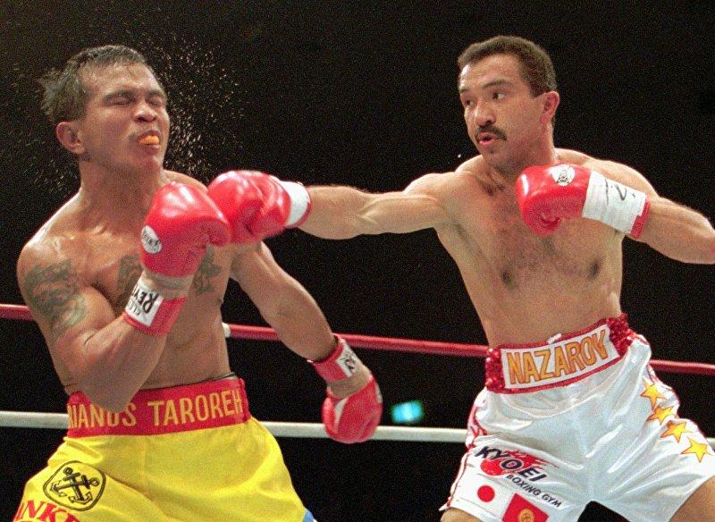 Чемпион Орзубек Назаров из Кыргызстана бьет по лицу Адриана Тарореха из Индонезии во время второго раунда 12-раундового бокса в Токио. 15 апреля 1996 года