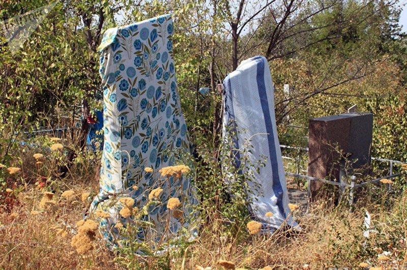 Надгробная плита прикрытая материалорм на юго-западном кладбище Бишкека