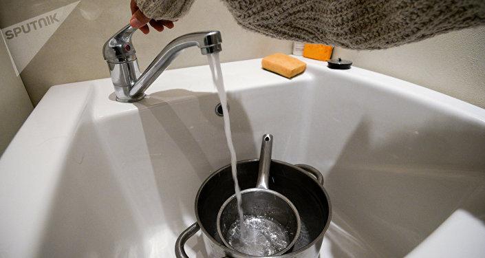 Девушка набирает холодную воду для кипячения. Архивное фото