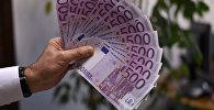 Мужчина держит в руке купюры на 500 евро. Архивное фото
