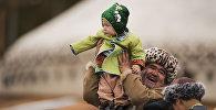 Мужчина в национальной одежде с ребенком. Архив