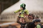 Мужчина с ребенком в национальном костюме. Архивное фото