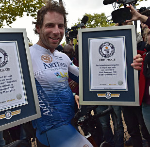 Британский велосипедист Марк Бомонт c фотографиями рекорда Гиннеса после прибытия в Триумфальную арку в Париже. 18 сентября 2017 года