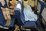 Мужчины спят на пассажирских сидениях самолета. Архивное фото