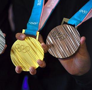 Медали зимней Олимпиады 2018 года демонстрируются юными южнокорейскими спортсменами во время открытия на церемонии в Сеуле. 21 сентября 2017 года