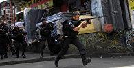 Полицейские занимают позицию во время операции после жестоких столкновений между наркобизнесами в трубе Росинья в Рио-де-Жанейро, Бразилия, 22 сентября 2017 года