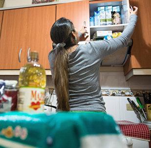 Женщина проверяет запасы продовольствия в кухонном шкафу. Архивное фото