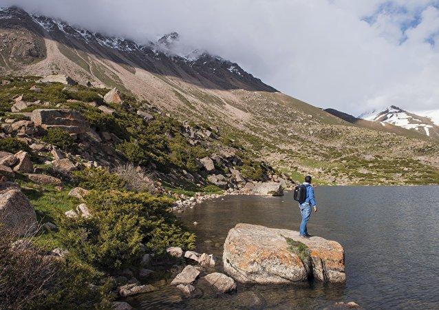 Кыргызстандын жаратылышына суктанган турист. Архивдик сүрөт