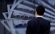 Бизнесмен смотрит на экран с фотографией банкноты США. Архивное фото