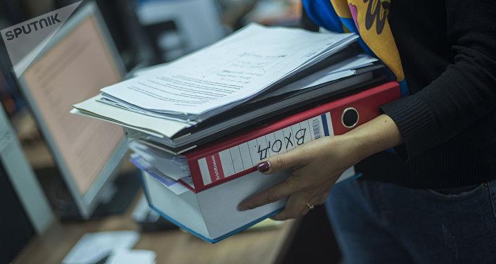 Девушка со стопкой документов в руках. Архивное фото