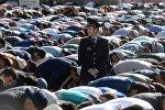 Сотрудник правоохранительных органов перед намазом в день праздника перед мечетью в Москве. Архивное фото