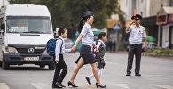 Инспектор проводит детей через дорогу во время рейда в Бишкеке. Архивное фото