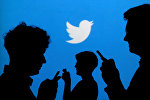 Люди с телефонами на фоне логотипа Twitter. Архивное фото