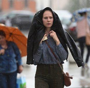 Прохожие идут по улице во время дождя. Архивное фото