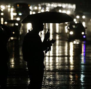 Человек с зонтом, ждет под дождем. Архивное фото