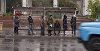 Горожане ждут на остановке транспорт во время дождя в Бишкеке. Архивное фото