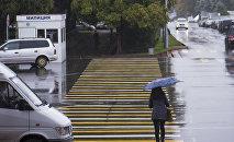 Девушка с зонтом переходит улицу в Бишкеке во время дождя