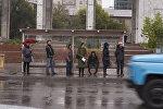 Горожане ждут транспорт на остановке во время дождя в Бишкеке. Архивное фото