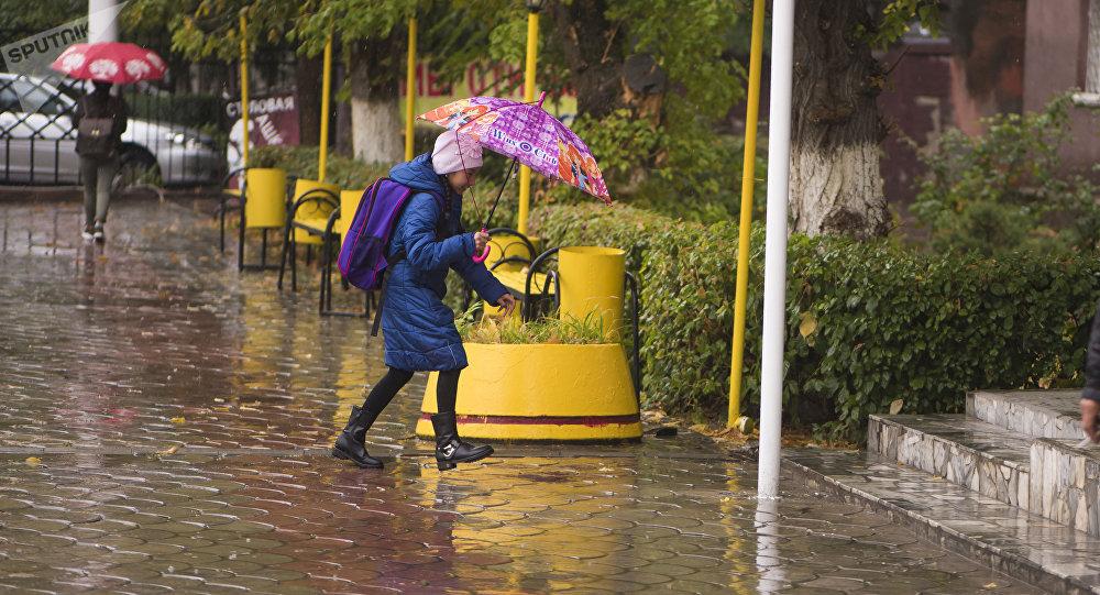 Девочка с зонтом идет по одной из улиц Бишкека во время дождя. Архивное фото