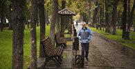 Мужчина идет по бульвару Эркиндик в Бишкеке во время дождя. Архивное фото
