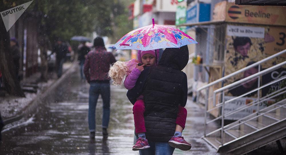 Мужчина с девочкой идут по одной из улиц Бишкеке во время дождя. Архивное фото