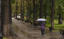 Женщина идет по бульвару Эркиндик в Бишкеке во время дождя. Архивное фото