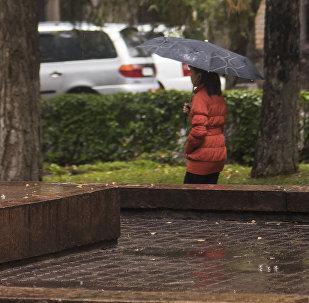 Девочка с зонтом идет по бульвару Эркиндик в Бишкеке во время дождя. Архивное фото