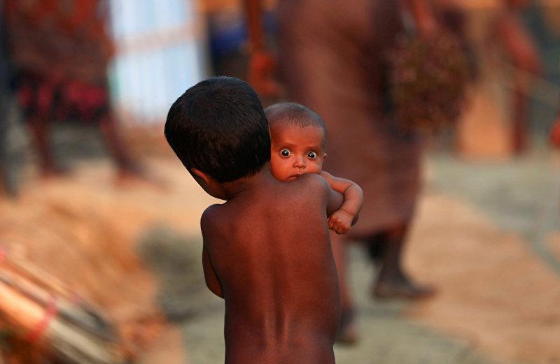 Мальчик несет младенца в лагере беженцев-рохинджа в Паланге Хали около Базара Кокса, Бангладеш, 4 октября 2017 года