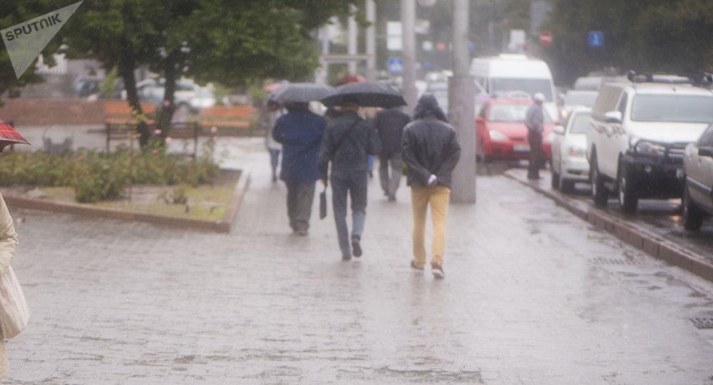 Прохожие на одной из улиц Бишкека во время дождя