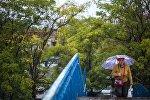 Женщина переходит мост в Бишкеке во время дождя. Архивное фото