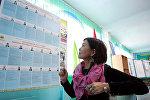 Женщина смотрит на информационный бюллетень президентских выборов на избирательном участке в поселке Кызыл-Бирлик возле Бишкека. Архивное фото