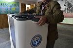 Мужчина двигает электронную урну в избирательном участке. Архивное фото