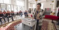 Женщина опускает бюллетень в урну на выборах в Кыргызстане. Архивное фото