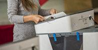 Девушка во время голосования на избирательном участке №1060 Бишкека в ходе выборов президента Кыргызстана