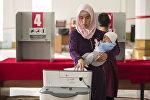 Женщина с ребенком во время голосования на избирательном участке №1060 Бишкека в ходе выборов президента Кыргызстана