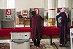 Избиратели в кабинке на избирательном участке. Архивное фото