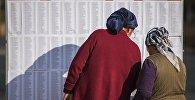 Женщины ищут свои фамилии в списке избирателей на избирательном участке в Бишкеке. Архивное фото