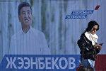 Женщина проходит мимо предвыборной агитации кандидата в президенты Сооронбаяна Жээнбекова в Бишкеке. 12 октября 2017 года
