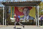 Мальчик проходит мимо предвыборного билборда парламента кандидата в президенты Омурбека Бабанова. Архивное фото