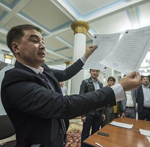 Наблюдатели во время подсчета голосов на избирательном участке во время выборов президента Кыргызстана