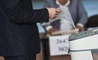 Избиратель с бюллетенем у электронной урны. Архивное фото