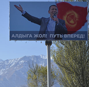 Лошади пасутся на поле рядом с щитом кандидата в президенты Кыргызстана Омурбека Бабанова. Архивное фото