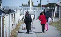 Женщины переходят контрольно-пропускного пункта Ак-Тилек на кыргызско-казахской границе
