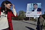 Женщины проходят мимо баннера агитирующий за кандидата в президенты КР Сооронбая Жээнбекова в Бишкеке. Архивное фото
