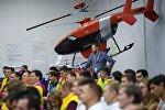 Участники XIX Всемирного фестиваля молодежи и студентов в Сочи слушают выступление министра промышленности и торговли РФ Дениса Мантурова. На втором плане: макет беспилотного вертолета VRT300 компании Вертолеты России.