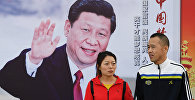 Люди проходят мимо плаката председателя КНР Си Цзиньпина в Пекине во время 19-ого Национального конгресса Коммунистической партии КНР в Пекине. 23 октября 2017 года