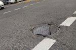 Сломанная крышка люка на дороге. Архивное фото